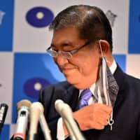 Former Defense Minister Shigeru Ishiba takes off his face mask as he attends a news conference to announce his candidacy for the LDP leadership in Tokyo on Tuesday. |  AFP