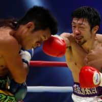 Akira Yaegashi punches Thailand's Wittawas Basapean during their IBF light flyweight title bout in Tokyo on Dec. 30, 2016. | REUTERS