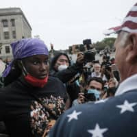 A demonstrator (left) and a supporter of U.S. President Donald Trump engage in verbal arguments in Kenosha, Wisconsin, on Tuesday.  | BLOOMBERG