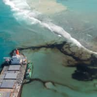 The bulk carrier ship MV Wakashio is seen run aground on a reef at Riviere des Creoles, Mauritius, on Aug. 11. | FRENCH ARMY COMMAND / VIA REUTERS