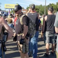 Aaron Danielson (center) wears a black T-shirt and a backpack at a pro-Trump rally in Portland, Oregon, on Saturday, hours before he was killed. | MIKE BAKER/THE NEW YORK TIMES