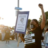 A demonstrator holds a sign reading 'Justice for Dijon' during a protest against the shooting of Dijon Kizzee by Los Angeles sheriff's deputies, in Los Angeles on Tuesday.  | REUTERS