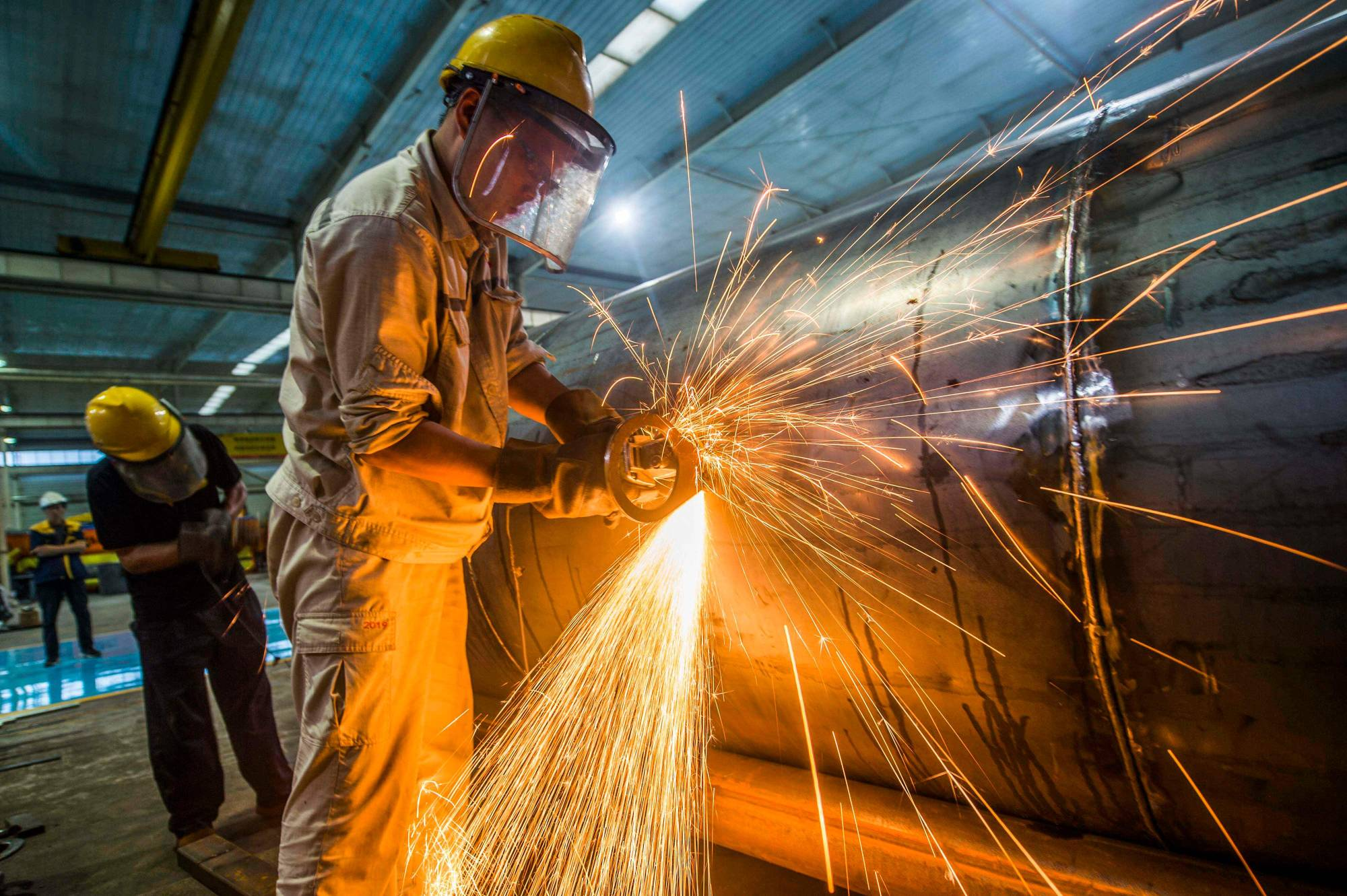 A worker welds medal truck parts at a factory in Weifang in China's eastern Shandong province. President Xi Jinping's new economic plan is for a more self-reliant domestic economy to serve as China's main growth driver, supplemented by foreign technologies and investment. | AFP-JIJI