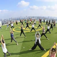 About 50 people take part in a morning yoga session on the rooftop of the Shibuya Sky building in Tokyo on Aug. 26, before going to work. | KYODO