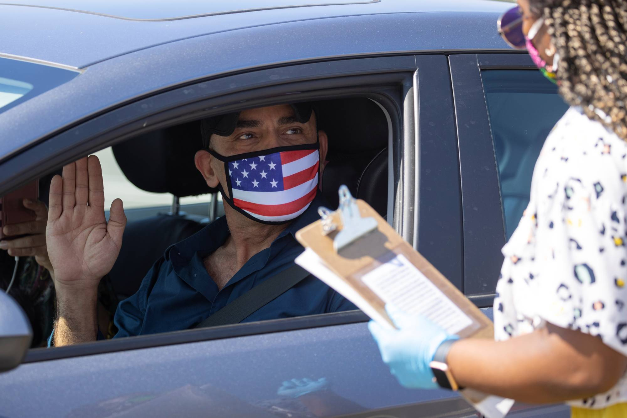 A U.S. immigration officer swears in a newly naturalized citizen in an empty parking amid the outbreak of the coronavirus disease in Santa Ana, California, in July. |  REUTERS