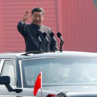Chinese President Xi Jinping waves from a vehicle as he reviews the troops at a military parade marking the 70th founding anniversary of People's Republic of China, in Beijing on Oct. 1. | REUTERS