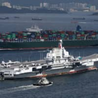 China's aircraft carrier Liaoning sails past a container ship as it enters Hong Kong in 2017. | REUTERS
