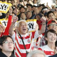Fans at a public viewing site in Fukuoka celebrate Japan's first try during its Rugby World Cup match against Scotland on Oct. 13, 2019. | KYODO