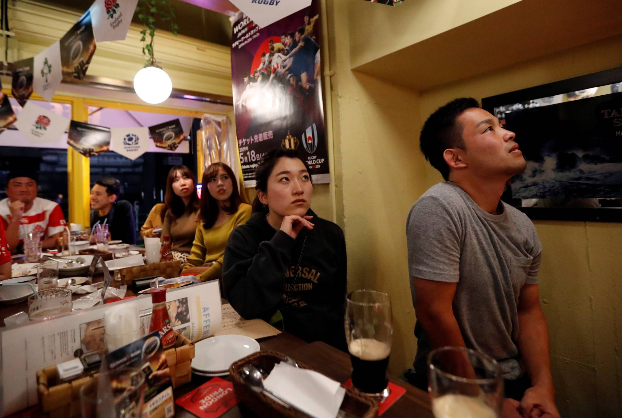 Fans watch the Rugby World Cup quarterfinal between Japan and South Africa in a bar in Tokyo on Oct. 20, 2019. | REUTERS