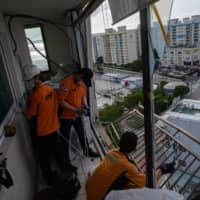 Fire department members secure a railing and air conditioning unit that were left hanging from a shattered apartment window in Busan, South Korea, due to high winds from Typhoon Maysak. | AFP-JIJI