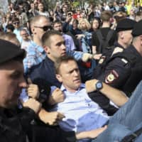 Russian police carry opposition leader Alexei Navalny (center) away from a demonstration against President Vladimir Putin in Moscow in May 2018.  | AP