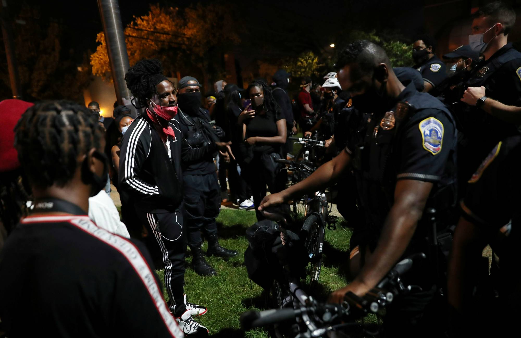 Protesters confront police officers outside of the 7th precinct on Wednesday to express their anger after Washington Metropolitan Police Department shot and killed a young black man in southeast DC. |  REUTERS