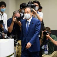 Chief Cabinet Secretary Yoshihide Suga arrives for a news conference in Tokyo on Wednesday to formally announce his bid to run in the Liberal Democratic Party's leadership election. | BLOOMBERG