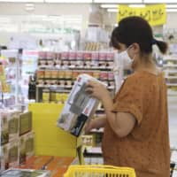 A woman buys a radio Friday at a hardware store in Tatsugo, Kagoshima Prefecture, along with other emergency supplies to prepare for Typhoon Haishen. | KYODO
