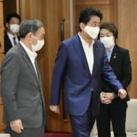 Prime Minister Shinzo Abe heads for a Cabinet meeting at the Prime Minister's Office Friday along with Chief Cabinet Secretary Yoshihide Suga (left). | KYODO