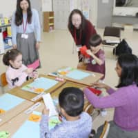 Teachers and children engage in a Japanese language class for overseas residents in Kani, Gifu Prefecture, in February. | KYODO