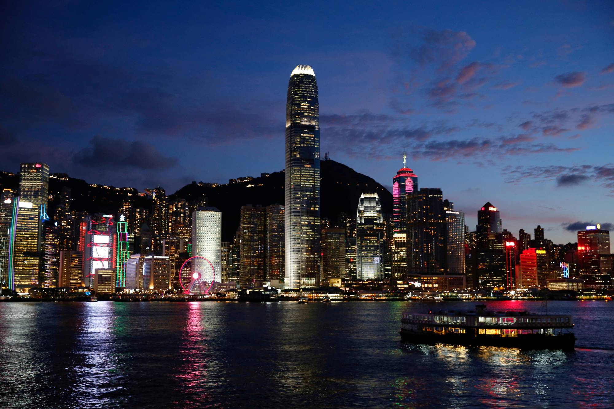 A boat crosses Victoria Harbour in front of a skyline of buildings during sunset in Hong Kong on June 29, 2020. | REUTERS