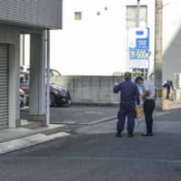 Kagawa police officers on Friday investigate a site in Takamatsu where a car had been parked the previous day with two girls inside who were later declared dead. | KYODO