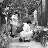 People offer flowers a year after the 1997 child murders in Kobe by a 14-year-old serial killer — who went by the notorious moniker of Seito Sakakibara. | KYODO