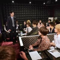 Full circle: Men working at host clubs in Tokyo's Kabukicho district gather for a poetry reading session in May of 2019.  | KYODO