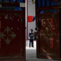 A Uighur child plays alone in the courtyard of a home at the Unity New Village in Hotan, in western China's Xinjiang region. | AP