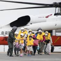 Residents of the village of Toshima, Kagoshima Prefecture, arrive at a heliport in the city of Kagoshima on Friday as they evacuate from the island in preparation for the approaching Typhoon Haishen. | KYODO