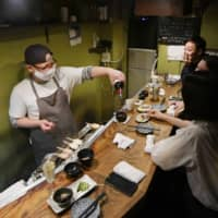 A master pours a drink at an eatery in Shinjuku's Golden Gai area in downtown Tokyo in mid-June. | KYODO