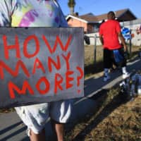 A man holds a sign stating 'How Many More?' at a makeshift memorial on Tuesday in Los Angeles, at the location where Black man Dijon Kizzee was shot and killed the previous day by Los Angeles Sheriff's Deputies.  | AFP-JIJI