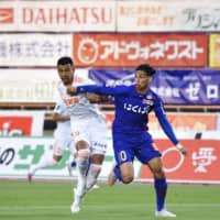 Kofu's Dudu (right) and Niigata's Gonzalo Gonzalez vie for the ball during a match on June 27 at Yamanashi Chuo Bank Stadium in Yamanashi Prefecture. | VENTFORET KOFU / KYODO