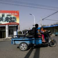 A Uighur woman shuttles schoolchildren as they ride past a propaganda poster showing Chinese President Xi Jinping joining hands with a group of Uighur elders in Hotan, in western China's Xinjiang region.  | AP