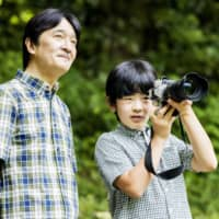 Prince Hisahito takes pictures as Crown Prince Akishino looks on at their residence in Tokyo's Akasaka district in August. | IMPERIAL HOUSEHOLD AGENCY / VIA KYODO