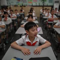 Elementary school students attend a class in Wuhan, China. China is recasting Wuhan as a heroic coronavirus victim and trying to throw doubt on the pandemic's origin story as it aims to seize the narrative at a time of growing global distrust of Beijing. | AFP-JIJI