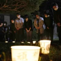 Officials of the Atsuma Municipal Government in Hokkaido offer prayers early Sunday morning in the town, exactly two years after a powerful earthquake. | KYODO