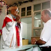 Joe Biden, then a U.S. senator, meets Catholic priest Zhang Depu in his church in Yanzikou Village, north of Beijing, in 2001.  | REUTERS