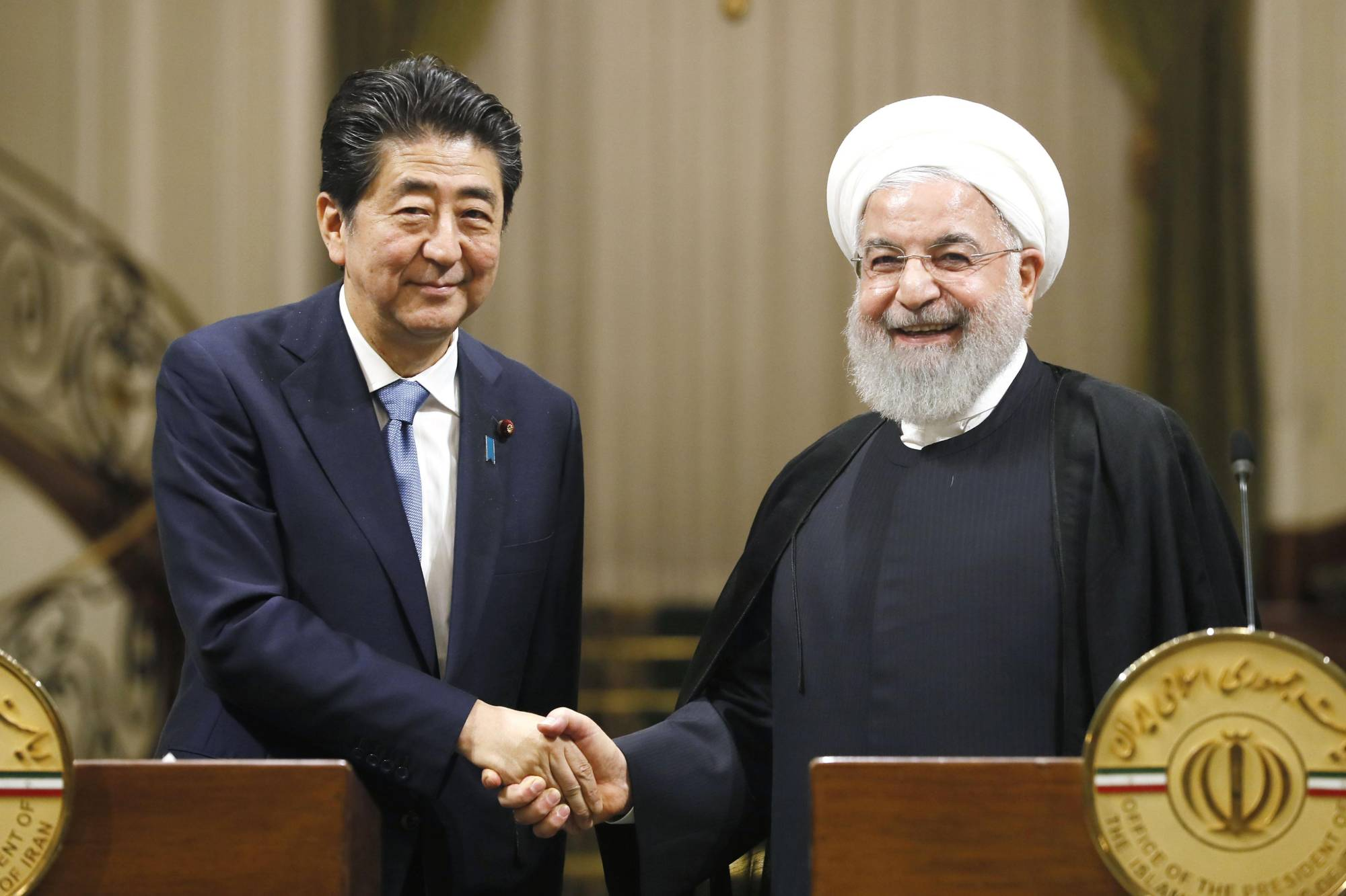 Prime Minister Shinzo Abe and Iranian President Hassan Rouhani shake hands after a joint press conference in Tehran on June 12. | KYODO