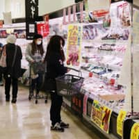 Shoppers buy food at a supermarket in Tokyo on April 8, a day after Prime Minister Shinzo Abe declared a state of emergency over the coronavirus pandemic.   KYODO