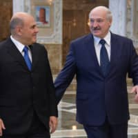 Russian Prime Minister Mikhail Mishustin (left) meets with Belarus President Alexander Lukashenko at the Independence Palace in Minsk on Thursday.  | SPUTNIK / VIA AFP-JIJI