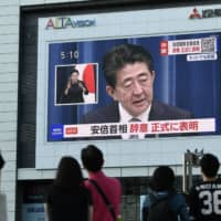 People watch a screen displaying a live broadcast of Prime Minister Shinzo Abe announcing his intention to resign. | BLOOMBERG