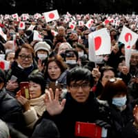 A crowd of well-wishers wave to Emperor Naruhito and Empress Masako during a public appearance for New Year's celebrations at the Imperial Palace in Tokyo on Jan. 2. The government plans to relax a rule limiting the size of crowds at professional sports, music and other events later this month amid signs that coronavirus cases are decreasing nationwide. | REUTERS