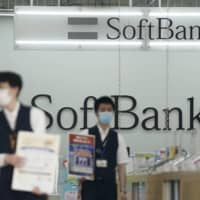 Sales staff wearing protective masks work at a SoftBank Corp. store in Tokyo. | BLOOMBERG