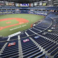 The Orix Buffaloes and the Rakuten Eagles play baseball inside an empty Kyocera Dome in June 2020 as virus-control measures limited crowds at sporting events. | KYODO