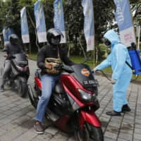 Health workers spray disinfectant at motorcycles as precaution against the coronavirus before a drive-in concert in Bali, Indonesia, in August.  | AP