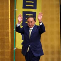 Chief Cabinet Secretary Yoshihide Suga waves as he officially kicks off his campaign rally for the presidential election of the ruling Liberal Democratic Party in Tokyo on Tuesday. | REUTERS
