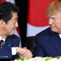 Prime Minister Shinzo Abe and U.S. President Donald Trump shake hands during a meeting in New York on the sidelines of the United Nations General Assembly in September 2019. | AFP-JIJI