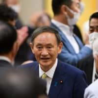 Chief Cabinet Secretary Yoshihide Suga talks with his supporters during a ceremony marking the beginning of his campaign for the Liberal Democratic Party leadership race in Tokyo on Tuesday. | BLOOMBERG