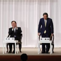 Chief Cabinet Secretary Yoshihide Suga (center), former Foreign Minister Fumio Kishida (right) and former Defense Minister Shigeru Ishiba attend a speech session for the Liberal Democratic Party's leadership election at its headquarters in Tokyo on Tuesday. | POOL / VIA AP
