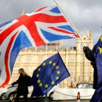 An anti-Brexit demonstrator waves a Union flag alongside a European Union flag outside the Houses of Parliament in London in 2018.  | AFP-JIJI