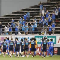 Sagan fans greet the players after their win over Yokohama FC on Saturday at Best Amenity Stadium in Tosu, Saga Prefecture. J. League and NPB clubs have been restricted to maximum attendances of 5,000 since professional sports resumed earlier this summer. | KYODO