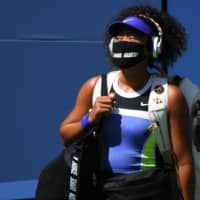 Naomi Osaka walks onto the court wearing a mask with the name of Ahmaud Arbery prior to her match against Marta Kostyuk on Friday in New York. | USA TODAY / VIA REUTERS