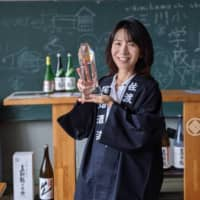 Rumiko Obata, executive vice president of Obata Sake Brewery, holds the Grand Prize trophy in the Satoyama category at Gakkogura brewery, which used to be an elementary school, on Sado Island, Niigata Prefecture.   OBATA SAKE BREWERY